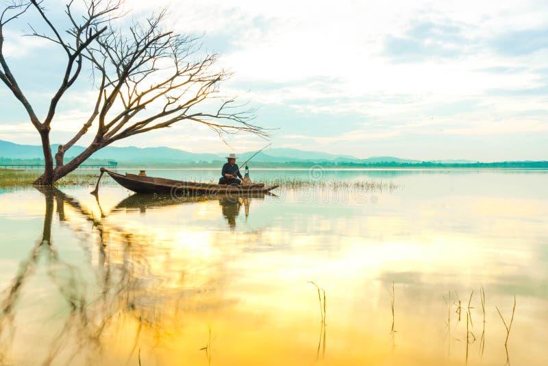 Silhouette du pêcheur à l'aide de l'hameçon se reposant dans le petit bateau et images libres de droits