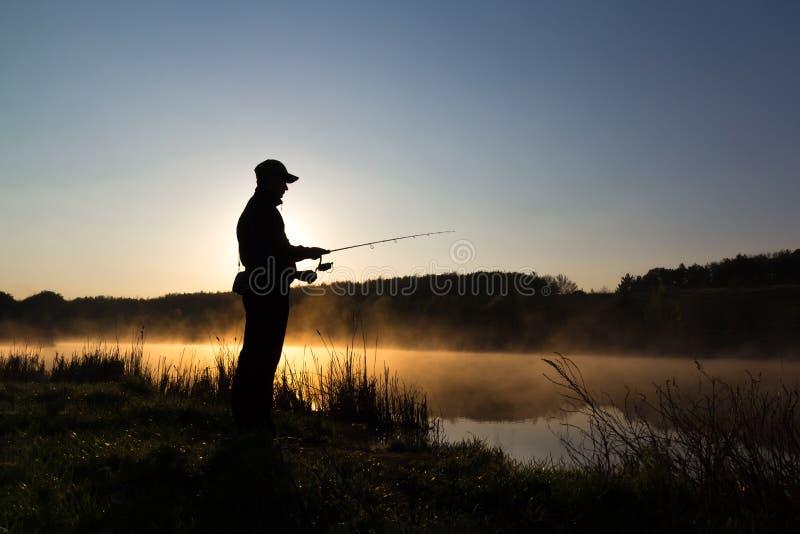 Silhouette du pêcheur aux poissons contagieux d'aube en rivière Matin froid et brume d'été au-dessus de la rivière photos libres de droits