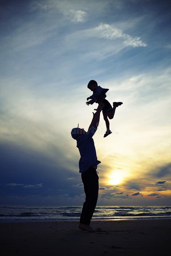 Silhouette du papa jetant en l'air vers le haut d'un enfant au coucher du soleil tandis que sta photo libre de droits