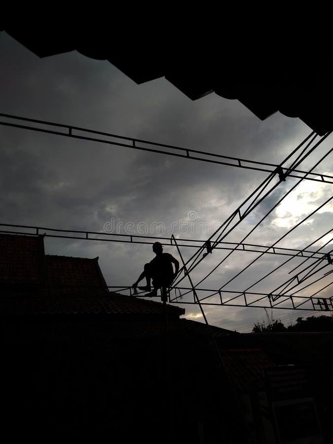 Silhouette du travailleur trois préparant la tente pour l'événement à venir d'heure images stock