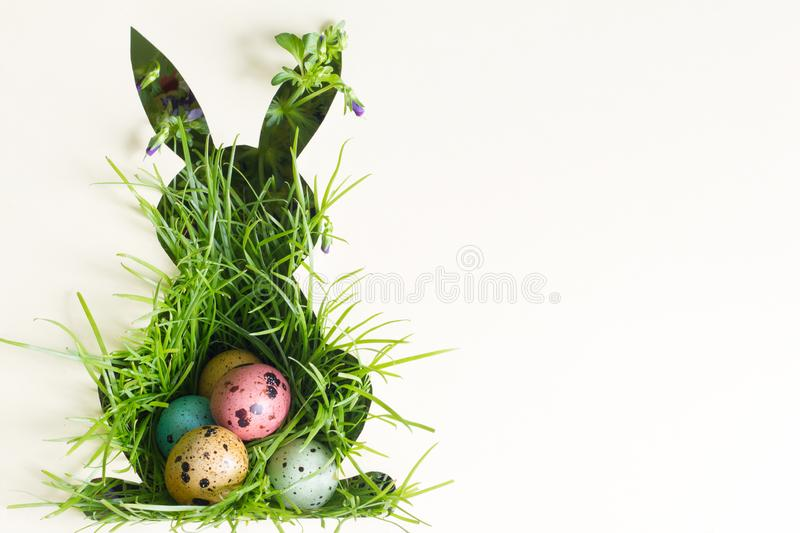 Silhouette of easter rabbit on paper with green grass and colorful egg abstract background. Closeup royalty free stock photo