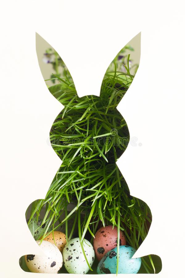 Silhouette of easter rabbit on paper with green grass and colorful egg abstract background. Closeup stock image