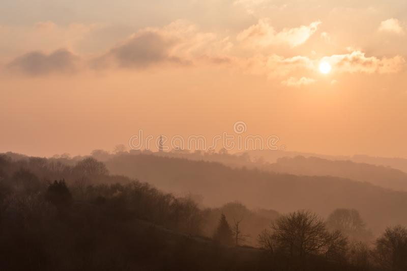 The silhouette of the Eastnor obelisk monument. Across the woods from the Malvern Hills. At sunset on a winters afternoon royalty free stock image