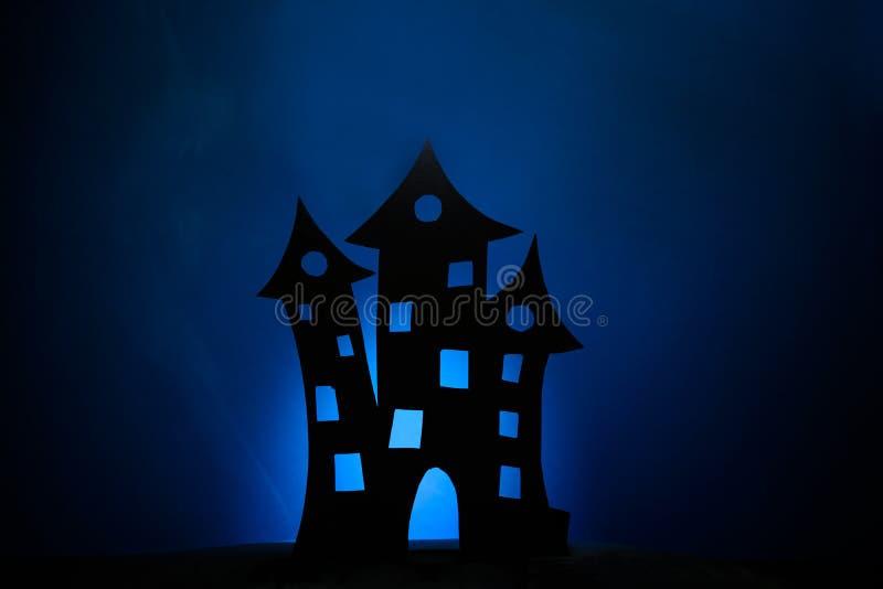 Silhouette effrayante de château, chauves-souris de papier noires et sorcière sur le vol de balai sur le fond bleu-foncé images libres de droits