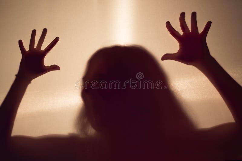 Silhouette effrayante femelle derrière un mur de tissu image libre de droits