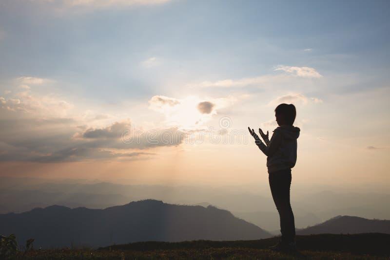 Silhouette einer Frau mit Händen in der Sonnenuntergangsidee für Religion, Anbetung, Gebet und Lob, religiöse Konzepte stockbild