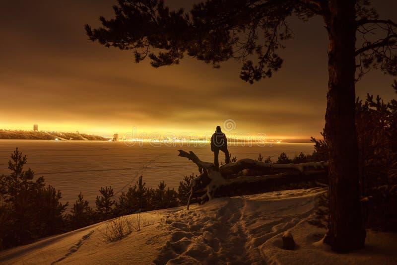 Silhouette eines Reisenden vor dem Hintergrund der Nachtstadt lizenzfreie stockfotos