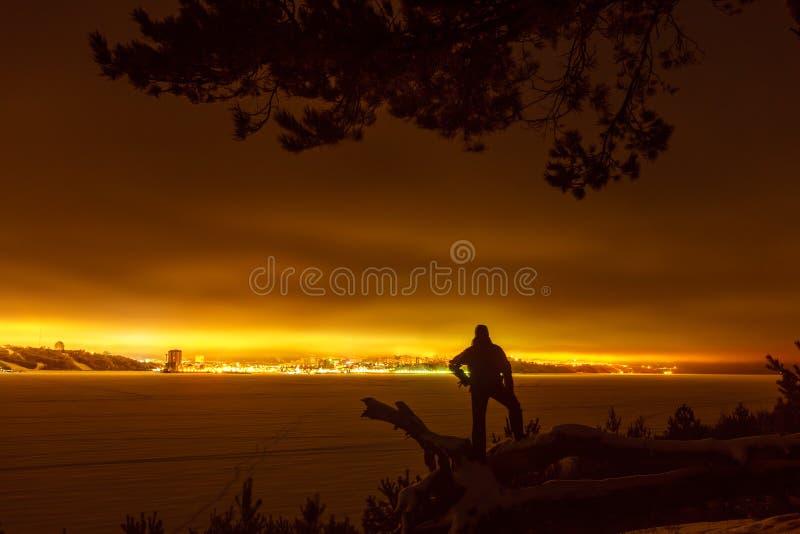 Silhouette eines Reisenden vor dem Hintergrund der Nachtstadt stockbilder