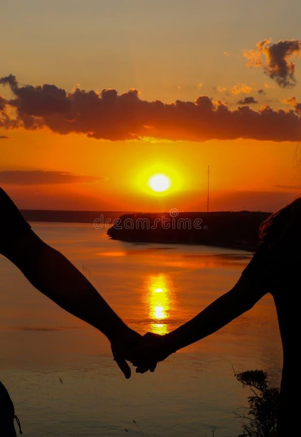 Silhouette eines romantischen Ehepaares, das am Strand Händen hält und den Sonnenuntergang über dem Meer betrachtet, das Konzept  stockfotos