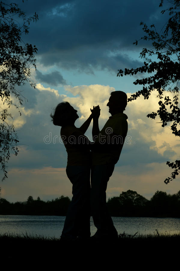 Silhouette of an elderly couple stock photo