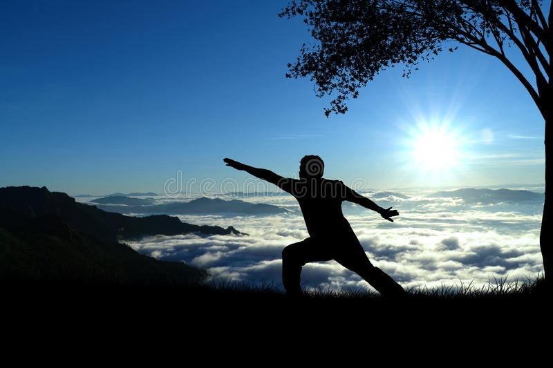 Silhouette man doing yoga on the mountain royalty free stock images