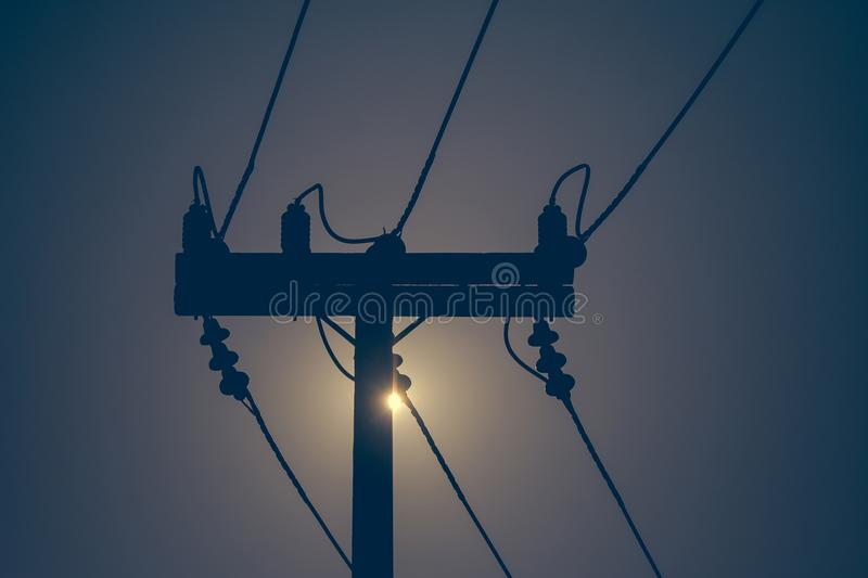 Silhouette of electricity pole and high voltage power line with sunset in the background. royalty free stock images