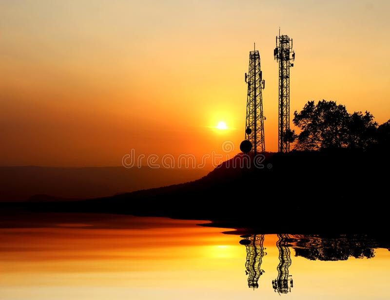 Silhouette electricity pole. Telecommunication tower with sunset on sky background royalty free stock image