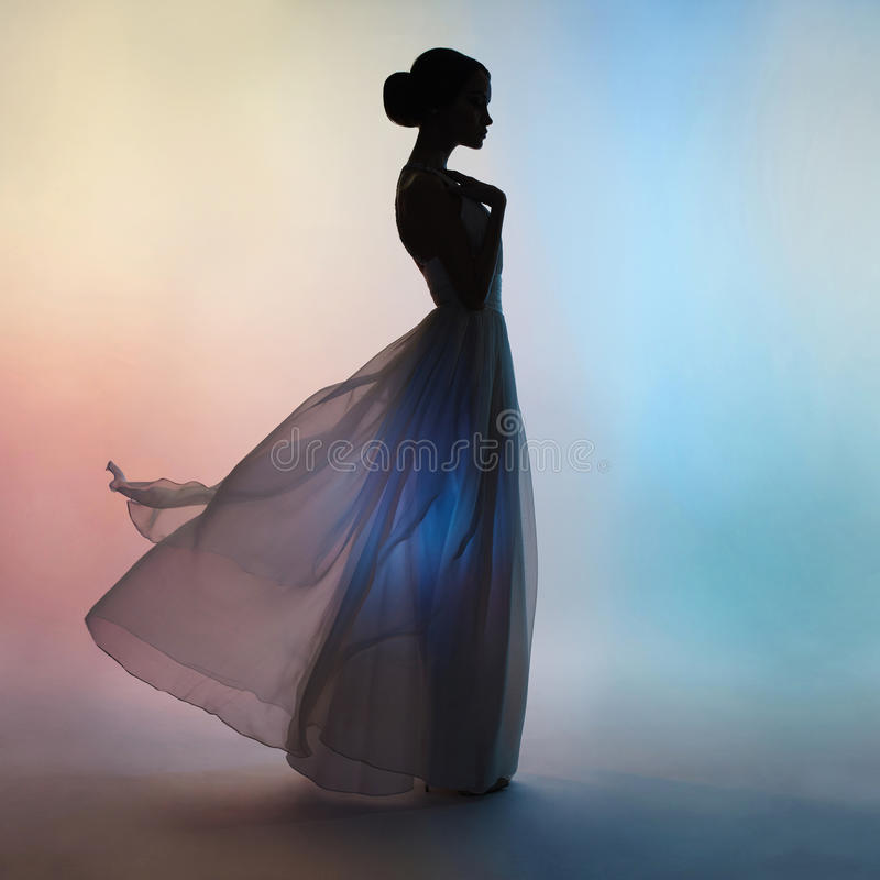 Silhouette elegant woman in blowing dress royalty free stock photos