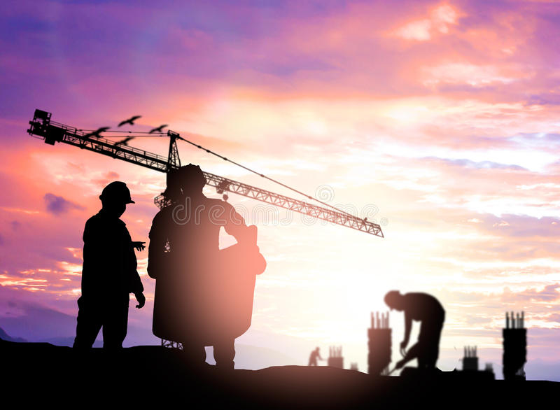 Silhouette engineer looking construction worker under tower cran in a building site over Blurred construction worker on construct royalty free stock image