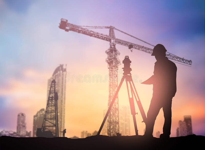 Silhouette engineer looking Loaders and trucks in a building sit. Silhouette black man survey and civil engineer stand on ground working in a land building site royalty free stock photos