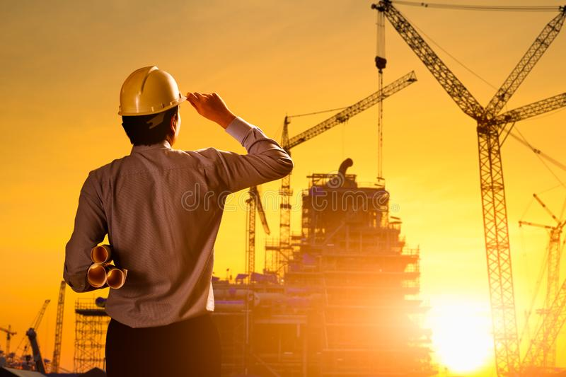Silhouette engineer. Wear a helmet at construction site with crane background and sunset royalty free stock images