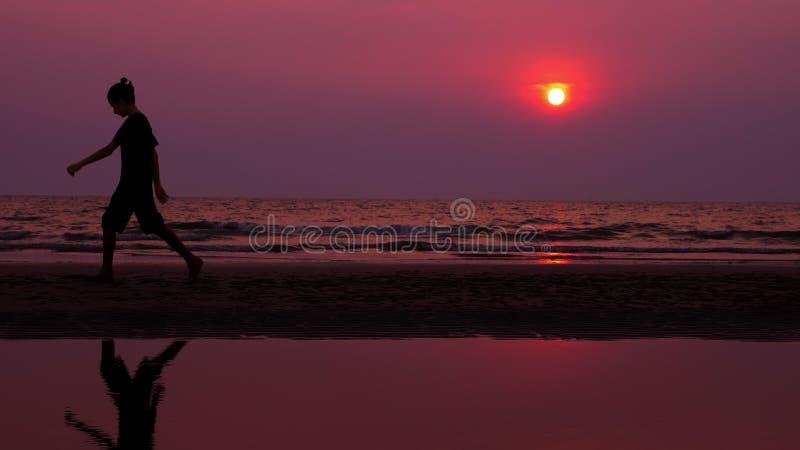 silhouette Ensam asiatisk ung man som fridfullt går längs en öde strand på solnedgången seascape arkivfoton