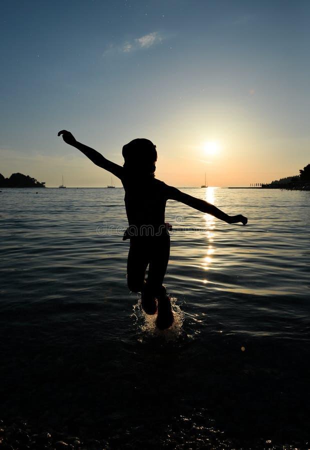 Silhouette et mer de fille Fille gaie de petit enfant sautant et planant dans le ciel sur le fond du ciel et de l'Adriatique s de images stock