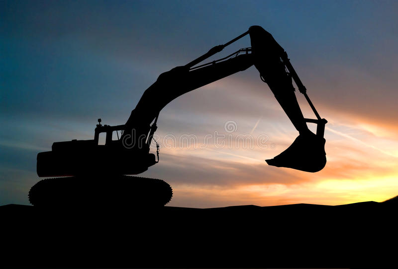 Silhouette of Excavator loader at construction site with raised stock photos