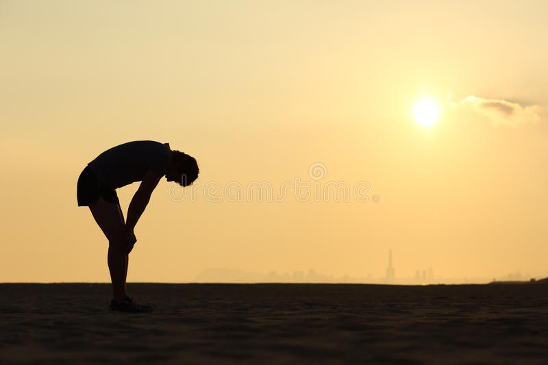 Silhouette of an exhausted sportsman at sunset stock photo