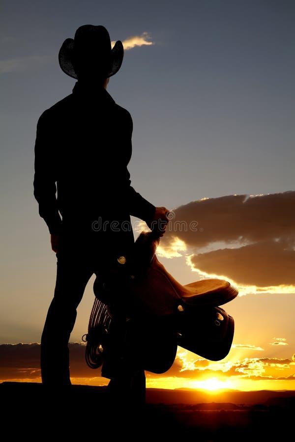 silhouette för cowboyholdingsadel arkivbild