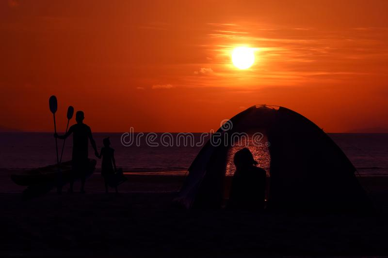 Silhouette family camping and kayaking on the beach with red sky sunset royalty free stock images