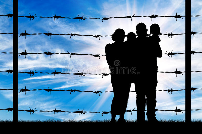 Silhouette of a family with children of refugees. Concept of refugee. Silhouette of a family with children of refugees and fence with barbed wire stock photo