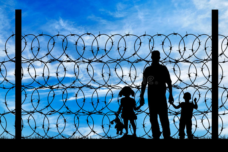 Silhouette of a family with children refugees. Silhouette of a family with children of refugees and fence with barbed wire on the background of the beautiful sky stock photo