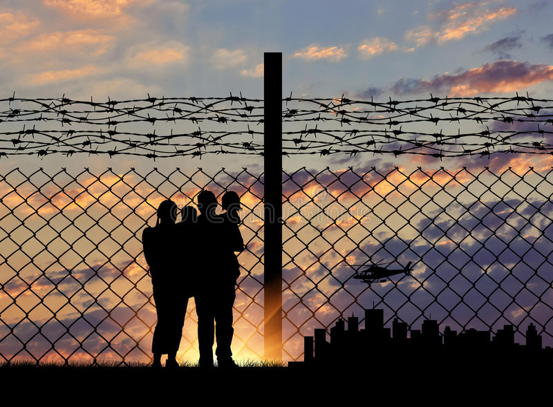 Silhouette of a family with children. Of refugees and fence with barbed wire on the background of evening city away stock image