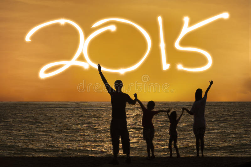 Silhouette of family enjoy new year. Silhouette of happy family on beach with number 2015 on the sky royalty free stock photos