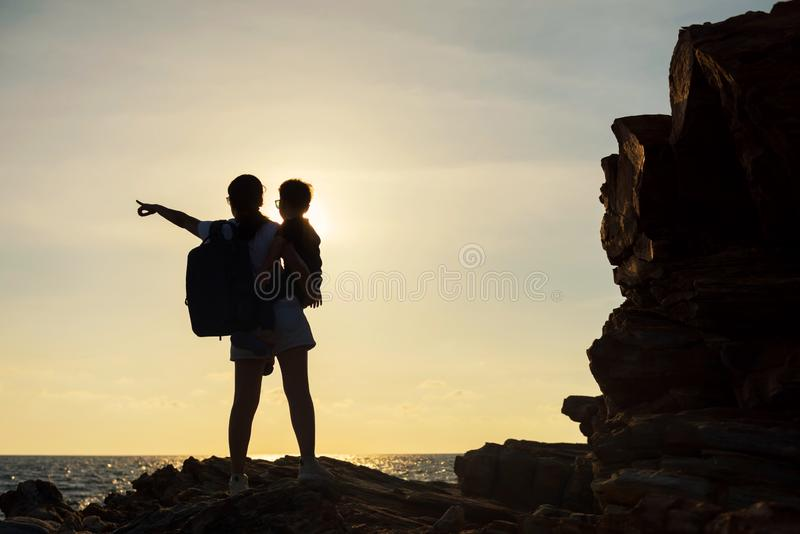 Silhouette family enjoy sunset and sea. Silhouette mother and little son looking at sea and sunset. Happy family standing on Natural stone arch at Khao Laem Ya royalty free stock image