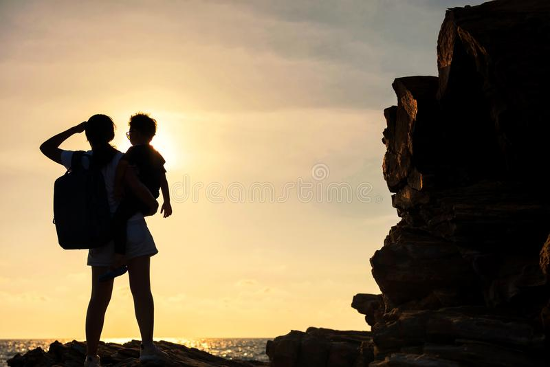 Silhouette family enjoy sunset and sea. Silhouette of mother holding her child son looking at ocean sea and sunset. Happy family standing on Natural stone arch royalty free stock image