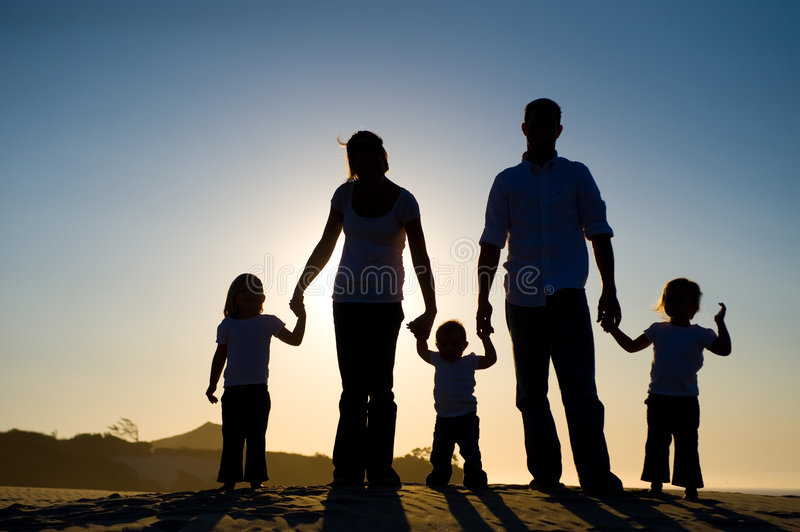 Silhouette of a family of five. Beautiful silhouette of a family, with the sun setting behind them, standing on a hill stock image