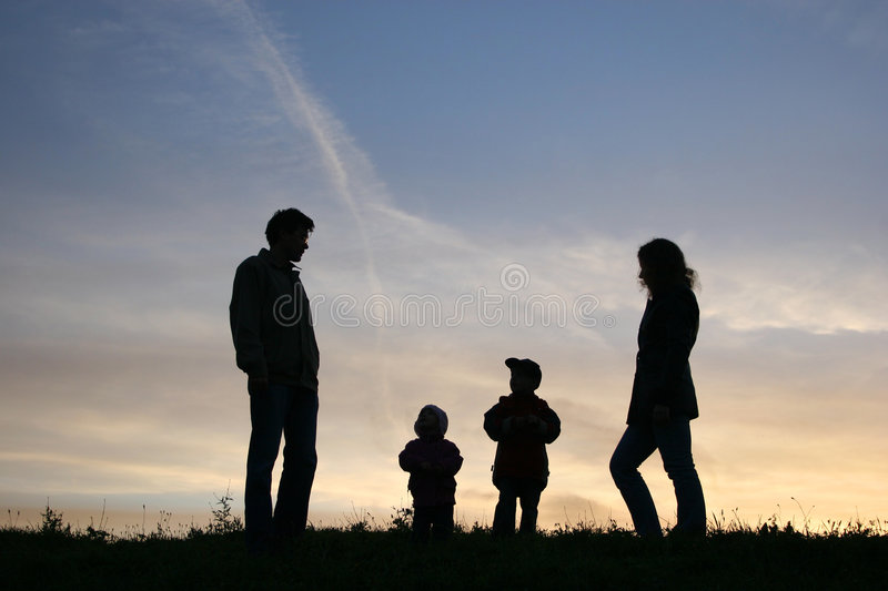 Silhouette family of four. Sunset stock image
