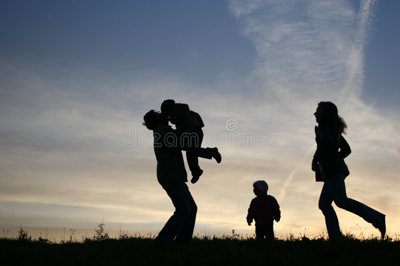 Silhouette family of four. Sunset stock photography