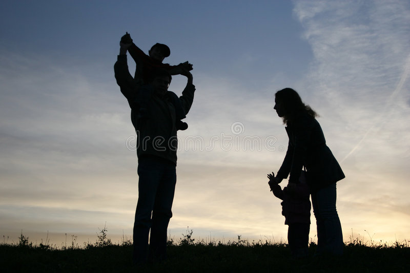 Silhouette family of four. Sunset royalty free stock photos