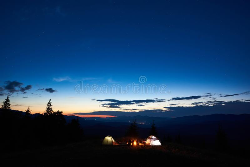 Family hikers having a rest at night camping in mountains. Silhouette of family hikers mother, father, two children enjoying at camping in mountains, beside royalty free stock image