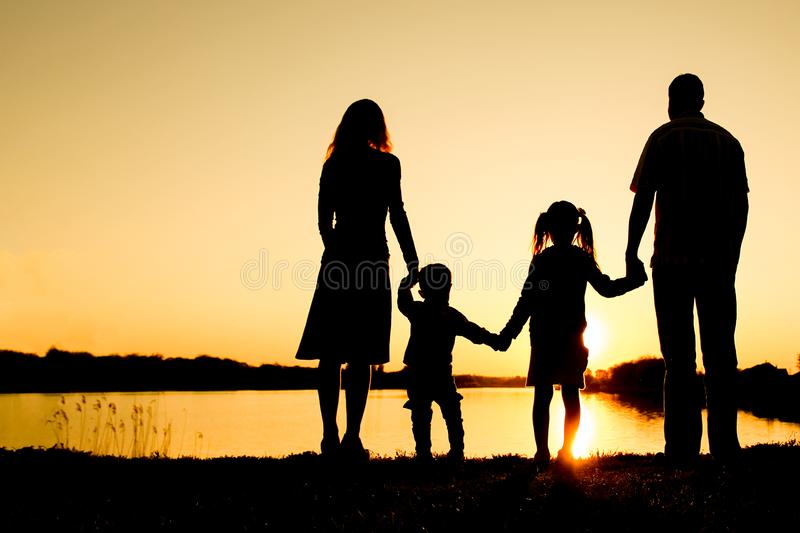 Silhouette family, including his father, mother and two children in the hands of. A silhouette family, including his father, mother and two children in the hands royalty free stock photo