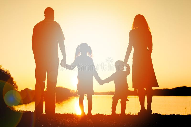 Silhouette family, including his father, mother and two children in the hands of. A silhouette family, including his father, mother and two children in the hands royalty free stock image