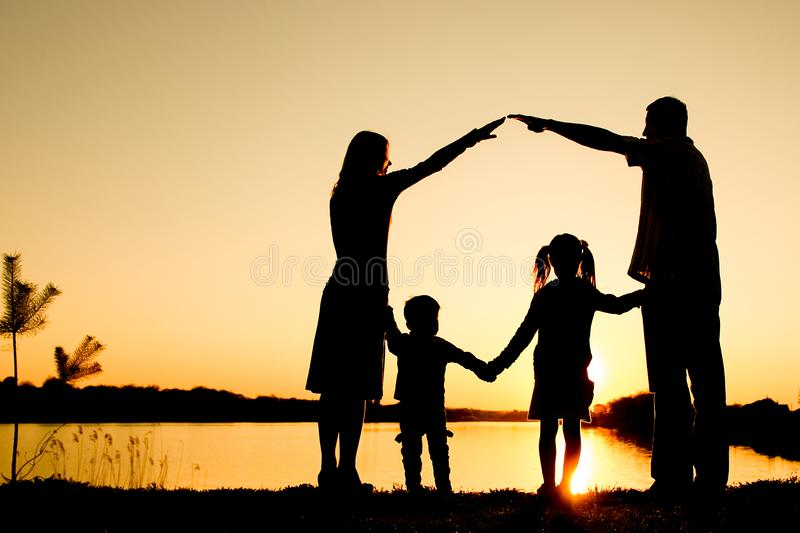 Silhouette family, including his father, mother and two children in the hands of. A silhouette family, including his father, mother and two children in the hands royalty free stock photography
