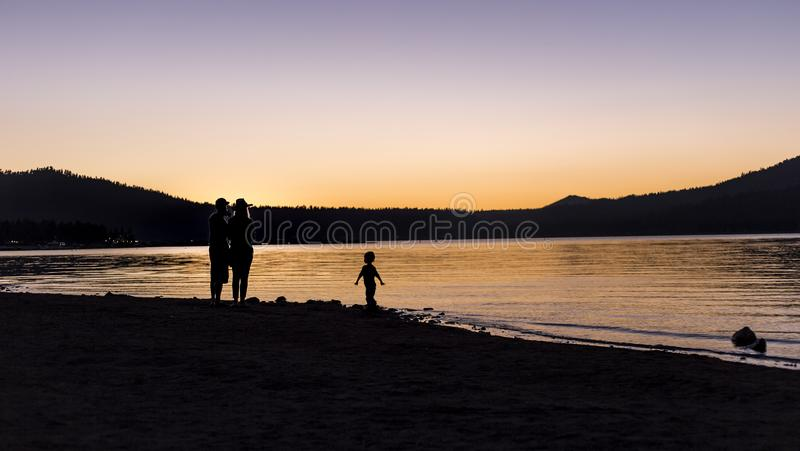 Silhouette of Family at a Lake. Silhouette of parents with a child watching the sunset over a lake. The family is hiking or camping outdoors stock images