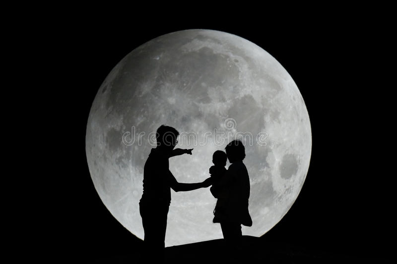 Silhouette of family with moon. Silhouette of father, mother and child with moon in the night - family royalty free stock image