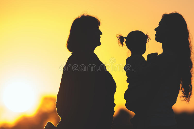 Silhouette family with mother, daughter and grandmother outdoor. Fall season. Silhouette of happy family with mother, daughter and grandmother outdoor. Fall stock photography