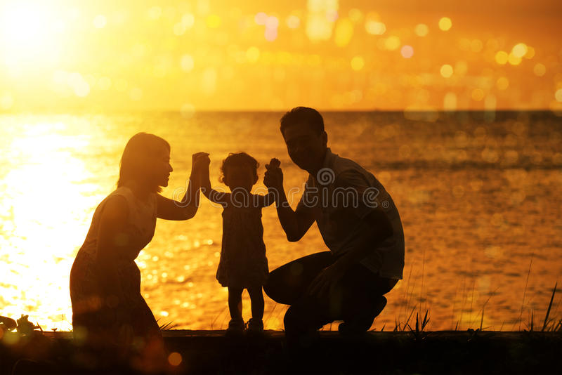 Silhouette family in outdoor sunset. Silhouette of Asian family outdoor activity, enjoying holiday together on coastline in beautiful sunset during vacations stock photo
