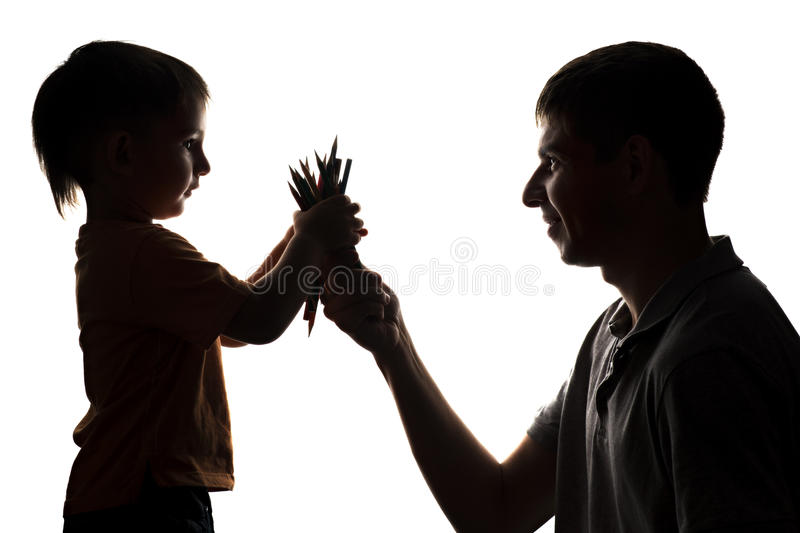 Silhouette of family relations, father gives the child color pencil. Silhouette of family relations of the father and the small son, the parent gives the child stock image