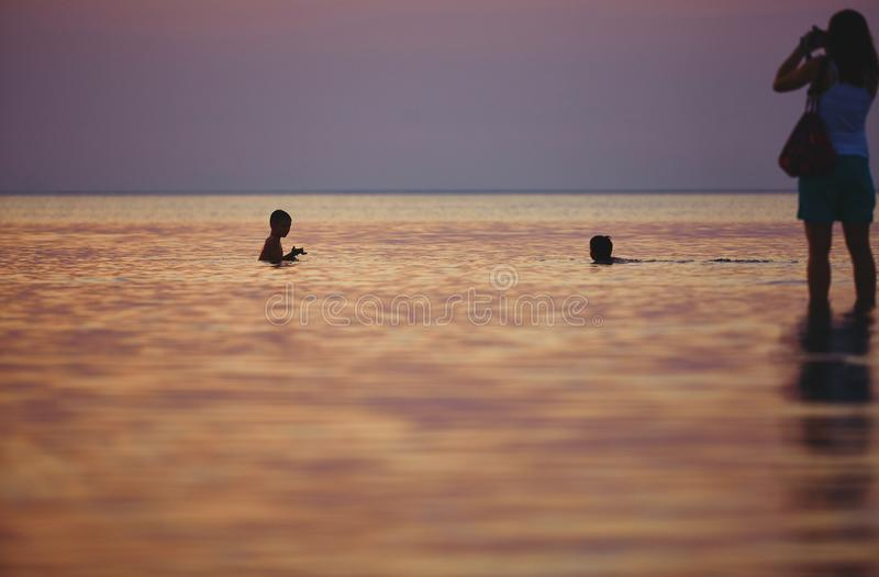 Silhouette of family in the sea against the sunset royalty free stock photo