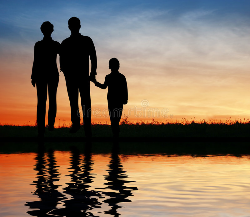 Silhouette family on sunset. Coast royalty free stock photography