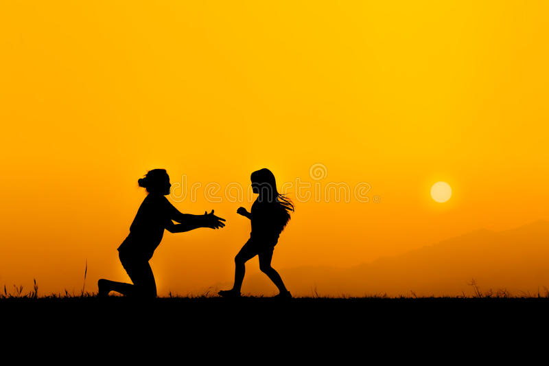 Silhouette of a family in sunset. Silhouette of a family and daughter running to mother on meadow, she enjoyed in sunset stock image