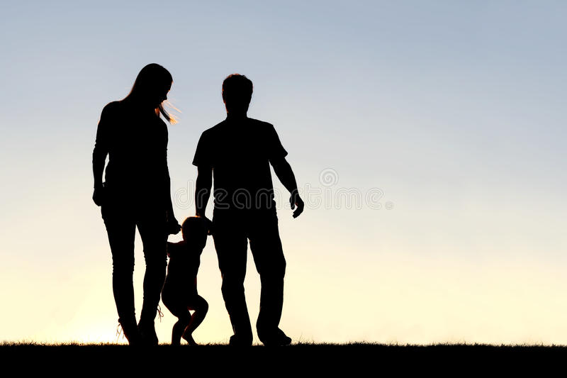 Silhouette of Family of Three People Walking at Sunset. A silhouette of a family of three people, including mother, father, and young child are playing around royalty free stock images